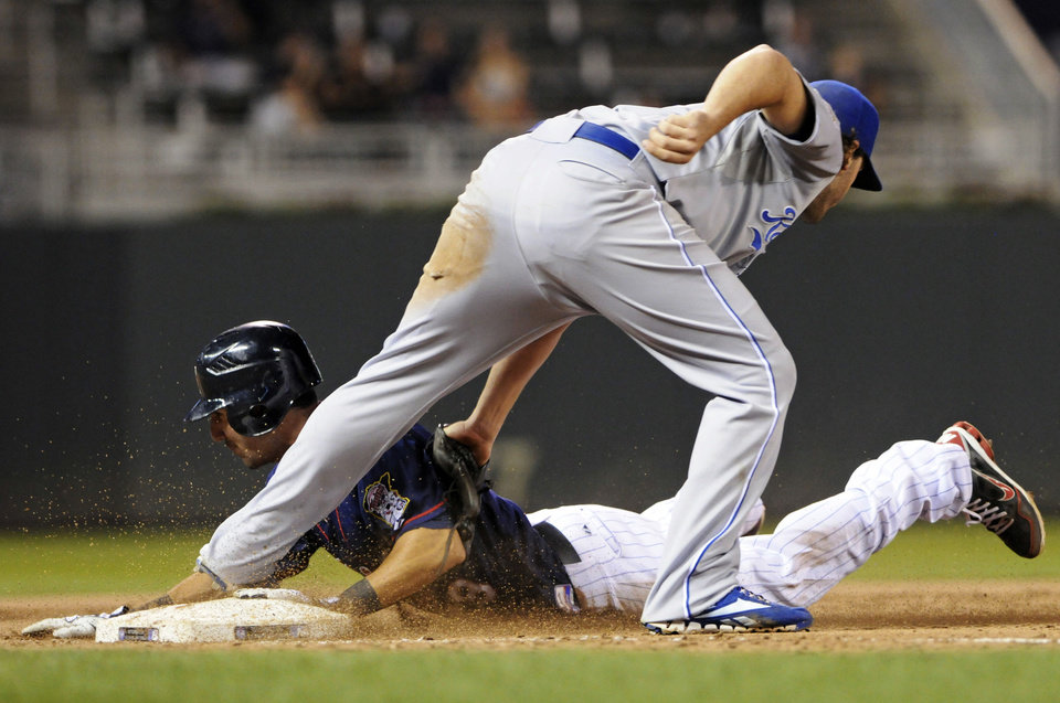 Photo -   Kansas City Royals third baseman Mike Moustakas, right, tags Minnesota Twins' Darin Mastroianni on an attempted steal of third base in the fifth inning of a baseball game, Tuesday, Sept. 11, 2012, in Minneapolis. (AP Photo/Jim Mone)