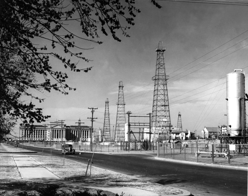 Photo - View of oil derricks running south from the Oklahoma State Capitol Building in the Lincoln Boulevard median.  View is looking north/northeast from a few blocks south of the capitol building.  Photo has date of 12/5/39 on back. File: Oil Fields/City/Drilling Zone Extension/Capitol Area