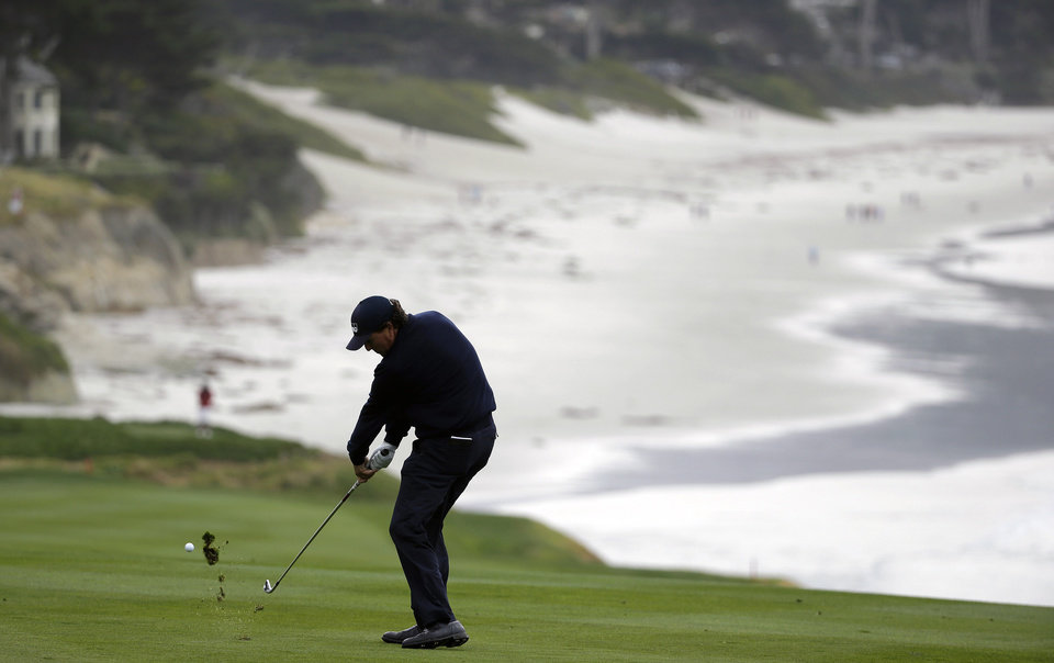 Photo - Phil Mickelson hits from the fairway down to the ninth green of the Pebble Beach Golf Links during the second round of the AT&T Pebble Beach Pro-Am golf tournament on Friday, Feb. 7, 2014, in Pebble Beach, Calif. (AP Photo/Eric Risberg)