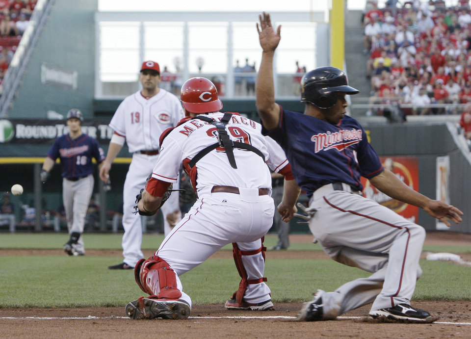 Photo -   Minnesota Twins' Ben Revere, right, scores as Cincinnati Reds catcher Devin Mesoraco (39) waits for the throw in the third inning of a baseball game, Friday, June 22, 2012, in Cincinnati. Revere scored on a sacrifice fly by Josh Willingham (16). First baseman Joey Votto (19) watches. (AP Photo/Al Behrman)