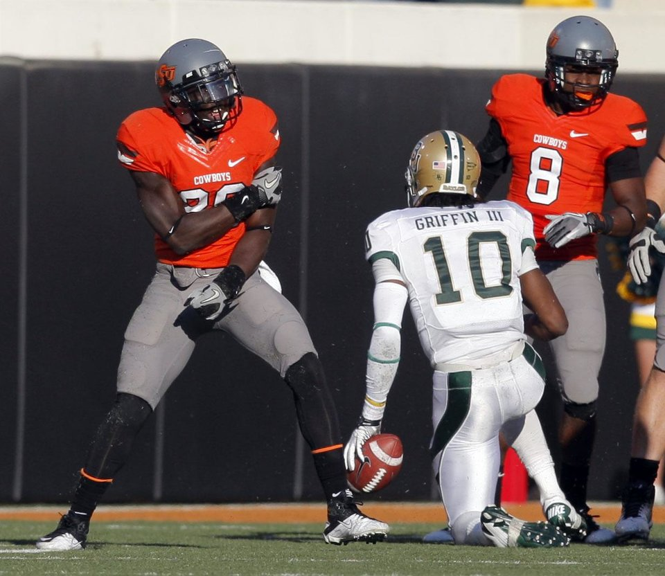 Photo - Oklahoma State's Larry Stephens (20)celebrates a sack on Baylor's Robert Griffin III (10) during a college football game between the Oklahoma State University Cowboys (OSU) and the Baylor University Bears (BU) at Boone Pickens Stadium in Stillwater, Okla., Saturday, Oct. 29, 2011. Photo by Sarah Phipps, The Oklahoman