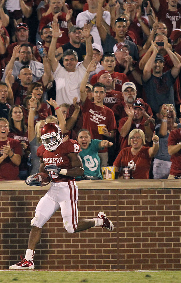 Photo -  Sooner fans celebrate after a touchdown by Oklahoma's Dominique Whaley (8) during the college football game between the University of Oklahoma Sooners (OU) and the Tulsa University Hurricanes (TU) at the Gaylord Family-Memorial Stadium on Saturday, Sept. 3, 2011, in Norman, Okla.  Photo by Chris Landsberger, The Oklahoman ORG XMIT: KOD