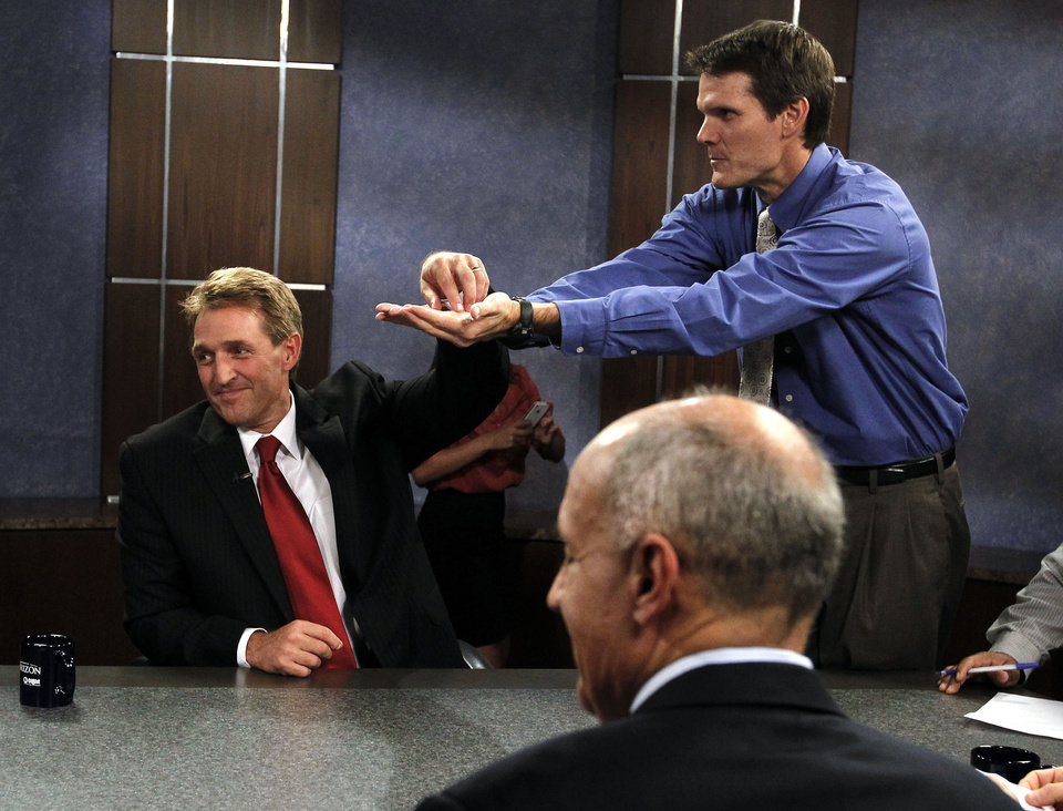To see who speaks first, Rep. Jeff Flake, R-Ariz., left, reaches for a piece of paper from David Majure, top right, executive producer at Eight, Arizona PBS, as Democrat Richard Carmona, front right, sits in the foreground in the studio prior to an Arizona U.S. Senate debate Wednesday, Oct. 10, 2012, in Phoenix. The candidates are vying for the seat left open by retiring Sen. Jon Kyl, R-Ariz. (AP Photo/Ross D. Franklin)