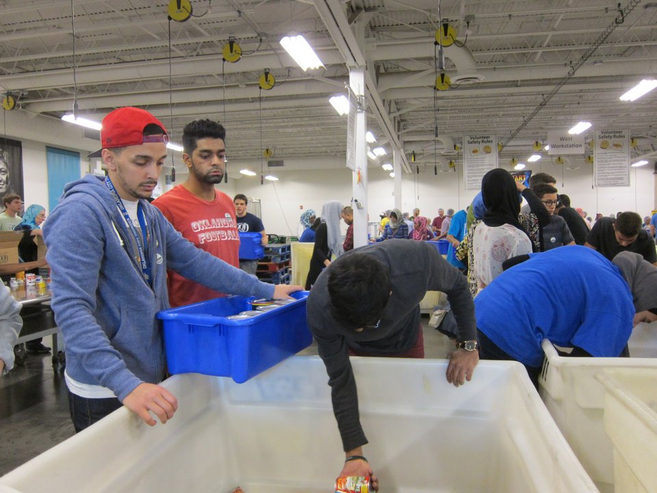 Photo -  Mohammad Ali Elyazgi,  Ammar Mahmood and Maarij Mahmood, all of Norman, sort canned goods at the recent Ramadan Day of Service at the Regional Food Bank of Oklahoma in Oklahoma City. Photo by Carla Hinton, The Oklahoman