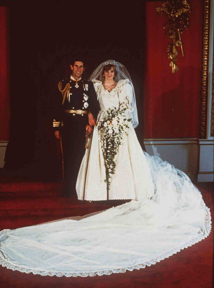 Photo - FILE-  This July 29, 1981 file photo shows Prince Charles and Princess Diana on their wedding day in London. Diana's 1981 gown by Elizabeth Emanuel helped usher in an era of opulence and formality. The shoulders were exaggerated, the skirt full and the sleeves pouffy. The train that trailed her was 25 feet long.    (AP Photo/FILE)
