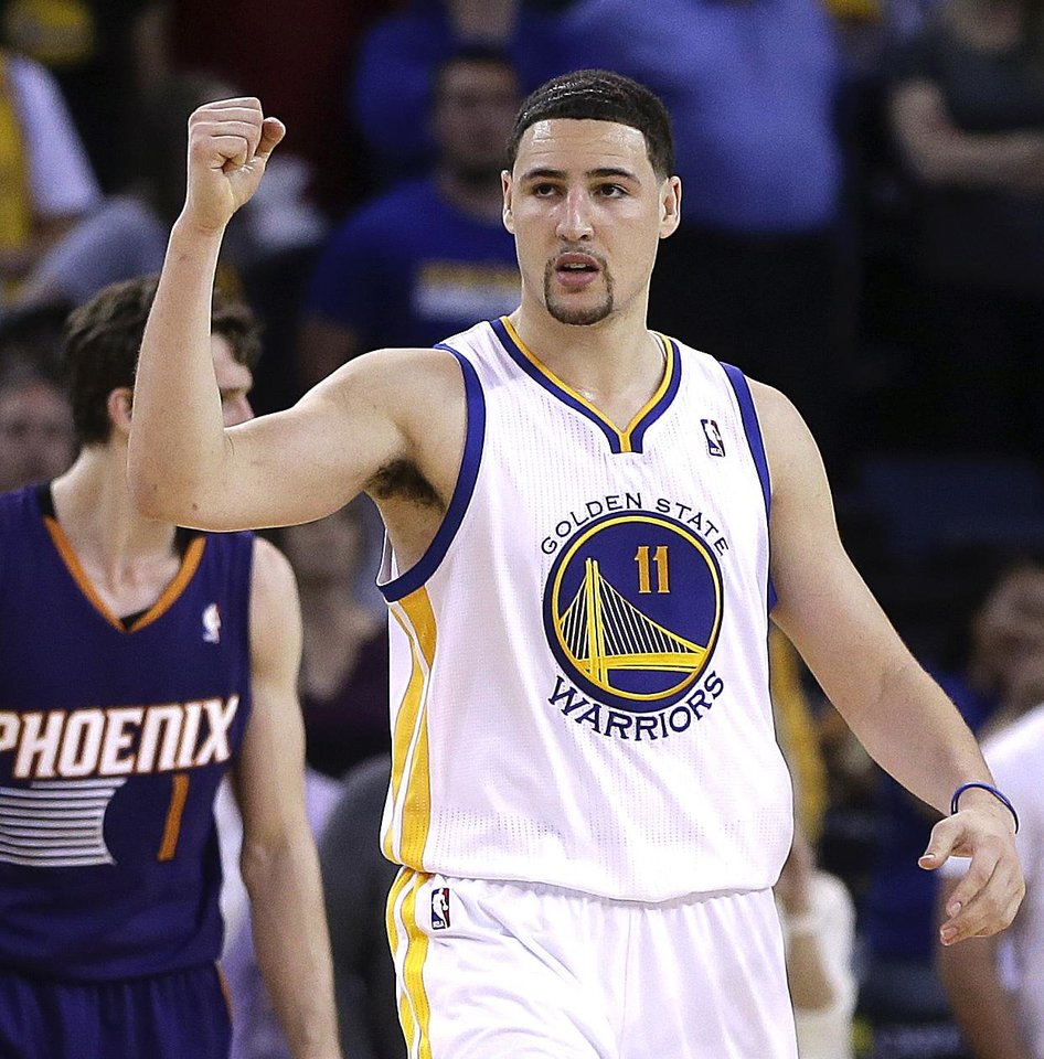 Photo - Golden State Warriors' Klay Thompson (11) celebrates a score against the Phoenix Suns during the second half of an NBA basketball game Sunday, March 9, 2014, in Oakland, Calif. (AP Photo/Ben Margot)