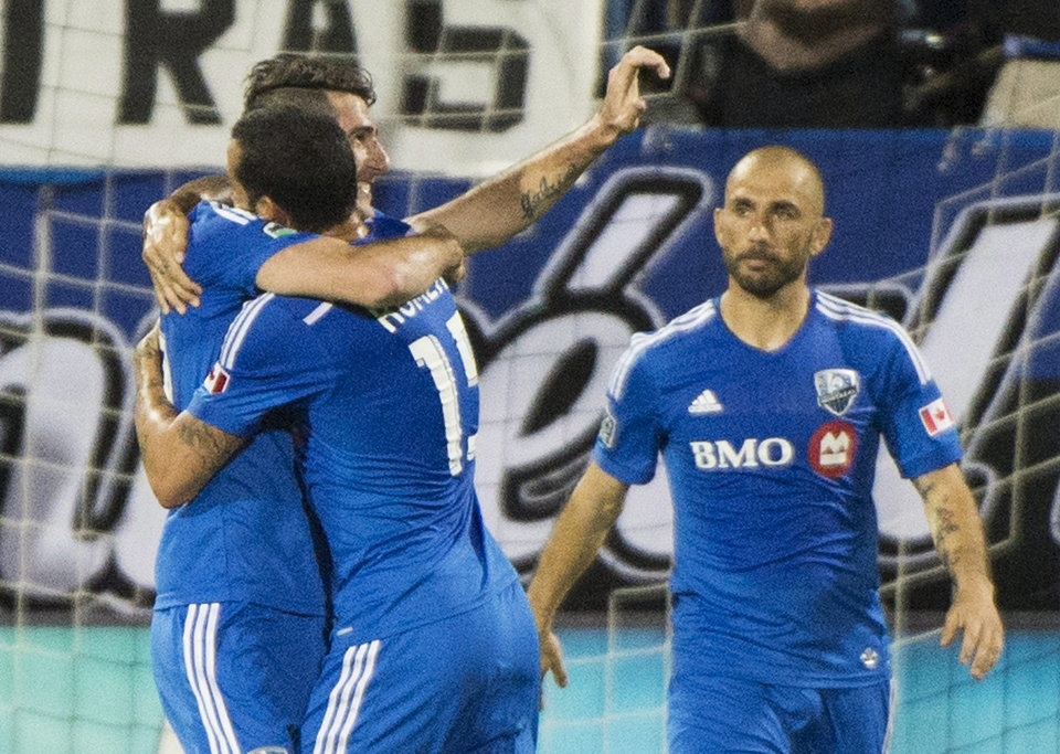 Photo - Montreal Impact's Ignacio Piatti, left, celebrates with teammates Dilly Duka (11) and Marco Di Vaio, right, after scoring against the Columbus Crew during first half MLS soccer action in Montreal, Saturday, Aug. 30, 2014. (AP Photo/The Canadian Press, Graham Hughes)