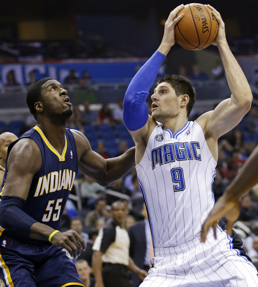 Photo - Orlando Magic's Nikola Vucevic (9), of Montenegro, looks for an open lane around Indiana Pacers' Roy Hibbert (55) during the first half of an NBA basketball game in Orlando, Fla., Sunday, Feb. 9, 2014. (AP Photo/John Raoux)