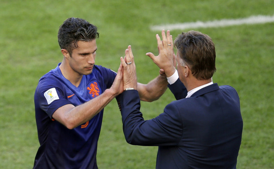 Photo - Netherlands' Robin van Persie, left, gives a high five to Netherlands' head coach Louis van Gaal after being substituted during the group B World Cup soccer match between Australia and the Netherlands at the Estadio Beira-Rio in Porto Alegre, Brazil, Wednesday, June 18, 2014.  (AP Photo/Michael Sohn)