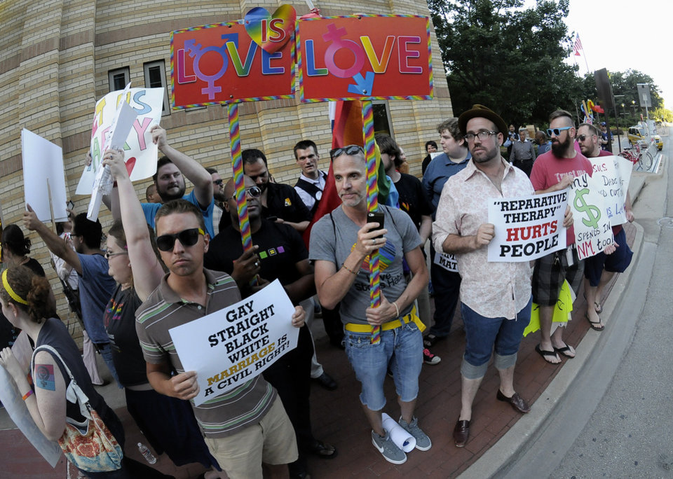Photo - People hold signs during a same sex marriage rally outside the Fort Worth Convention Center in Fort Worth, Texas, Thursday, June 5, 2014. The Texas GOP convention began in Fort Worth on Thursday.  (AP Photo/The Fort Worth Star-Telegram, Max Faulkner)  MAGS OUT