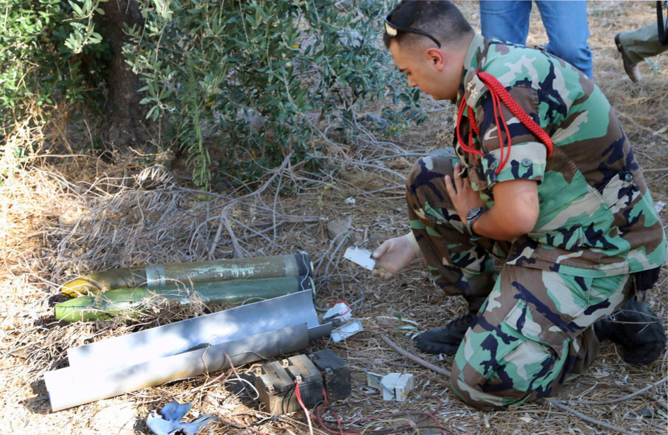 Photo - A Lebanese army expert dismantles two rockets that were found ready to fire into northern Israel, in the southern Lebanese village of Al-Mari, Lebanon, Friday, July. 11, 2014. The Lebanese army said in a statement that an