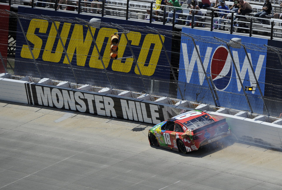 Photo - Kyle Busch wrecks along the wall during the NASCAR Sprint Cup Series auto race, Sunday, June 1, 2014, at Dover International Speedway in Dover, Del. (AP Photo/Nick Wass)