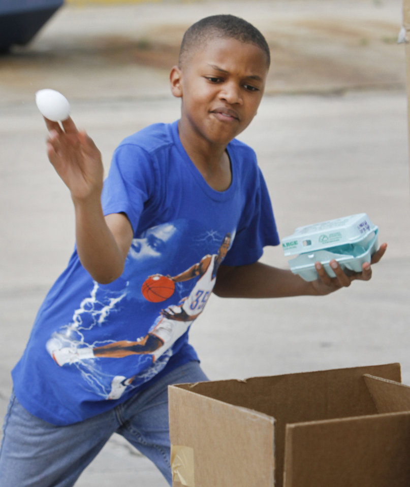 Matthew Jackson, 12, throws an egg filled with paint at a piece of paper at the Almonte Library. Oklahoma City libraries will offer activities throughout the coming summer. Photo By Steve Gooch, The Oklahoman <strong>Steve Gooch - The Oklahoman</strong>
