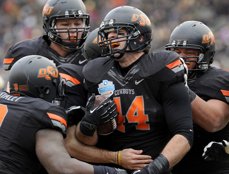 Photo - Oklahoma State tight end Jeremy Seaton (44) celebrates with teammates after a first-half touchdown against Purdue during the Heart of Dallas Bowl NCAA college football game, Tuesday, Jan. 1, 2013, in Dallas. (AP Photo/Matt Strasen)