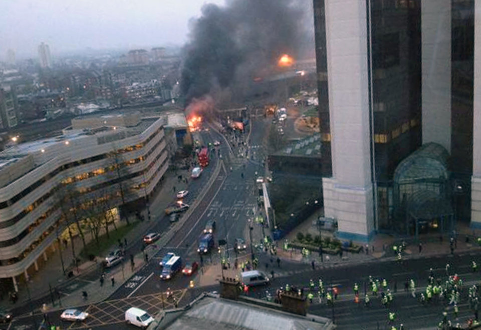 Photo - In this overhead view showing smoke and flames at the site of a helicopter crash in central London, as people gather to view the scene shortly after the incident, early Wednesday Jan. 16, 2013. Police say two people were killed when a helicopter crashed during rush hour in central London after apparently hitting a construction crane on the side of St. George's Tower. This photo was taken from an adjacent building to St. George's Tower which is out of shot right, and construction workers are seen gathering below right.  (AP Photo / Victor Jimenez, PA) UNITED KINGDOM OUT - NO SALES - NO ARCHIVES