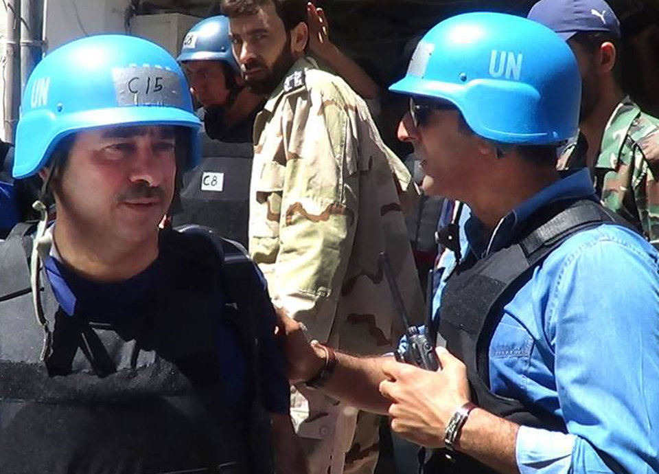 Photo - In this citizen journalism image provided by the United media office of Arbeen which has been authenticated based on its contents and other AP reporting, members of UN investigation team speak in Damascus countryside of Zamalka, Syria, Wednesday, Aug. 28, 2013. U.N. chemical weapons experts headed to a Damascus suburb on Wednesday for a new tour of areas struck by a purported poison gas attack, activists said, as Western powers laid the groundwork for a possible punitive strike and the U.N. chief pleaded for more time for diplomacy. (AP Photo/United media office of Arbeen)