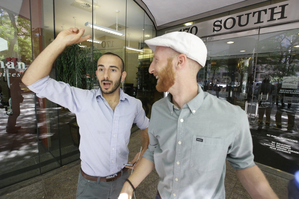 Photo - Plaintiffs Moudi Sbeity, left, and his partner Derek Kitchen, one of three couples who brought a lawsuit against Utah's gay marriage ban, celebrate as they arrive at their lawyer's office in Salt Lake City on Wednesday, June 25, 2014. A federal appeals court on Wednesday ruled for the first time that states must allow gay couples to marry, finding the Constitution protects same-sex relationships and putting a remarkable legal winning streak across the country one step closer to the U.S. Supreme Court. (AP Photo/Rick Bowmer)