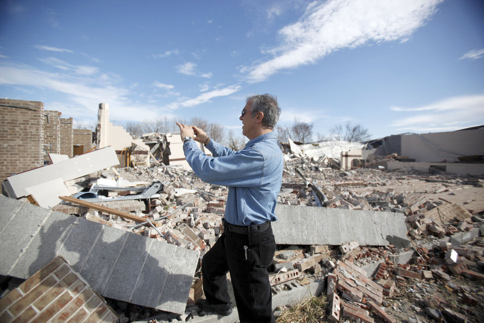 Photo - Allen Zahrai, with the National Severe Storms Laboratory, walks past debris at the Ardmore Adventist Academy near the Majestic Hills neighborhood north of Ardmore, Thursday, Feb. 12, 2009, PHOTO BY SARAH PHIPPS, THE OKLAHOMAN