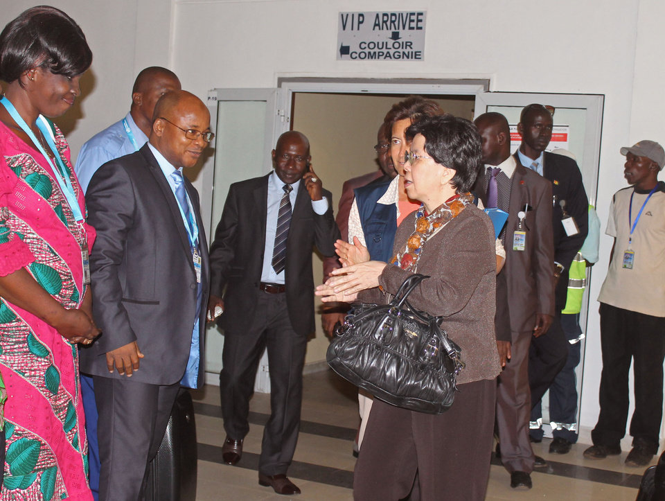 Photo - China's Margaret Chan, center, Director-General of the World Health Organization, WHO, is greeted by officials as she arrives at the airport for talks on Ebola in the city of Conakry, Guinea, Friday, Aug. 1, 2014. The death toll from the worst recorded Ebola outbreak in history surpassed 700 in West Africa as security forces went house-to-house in Sierra Leone's capital Thursday looking for patients and others exposed to the disease. Fears grew as the United States warned against travel to the three infected countries — Guinea, Sierra Leone and Liberia — and Sierra Leone's soccer team was blocked from boarding a plane in Nairobi, Kenya, that was to take them to the Seychelles for a game on Saturday. (AP Photo/ Youssouf Bah)