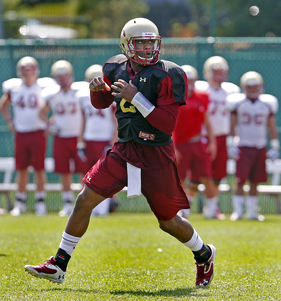 Photo - Boston College NCAA college football quarterback Tyler Murphy steps back after handing off the ball during practice on media day Thursday,  Aug. 7,  2014 in Boston. (AP Photo/Boston Herald, Nancy Lane) BOSTON GLOBE OUT. METRO BOSTON NEWSPAPER OUT. MAGS OUT. ONLINE OUT.