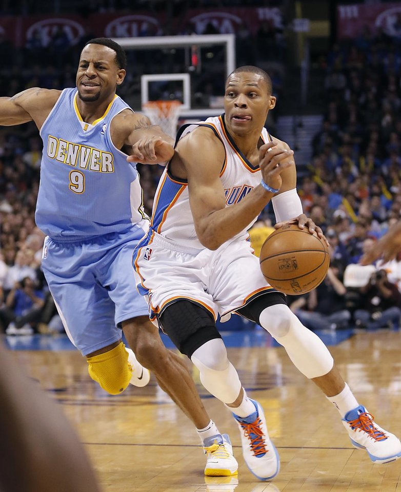 Oklahoma City's Russell Westbrook (0) drives past Denver's Andre Iguodala (9) during the NBA basketball game between the Oklahoma City Thunder and the Denver Nuggets at the Chesapeake Energy Arena on Wednesday, Jan. 16, 2013, in Oklahoma City, Okla.  Photo by Chris Landsberger, The Oklahoman