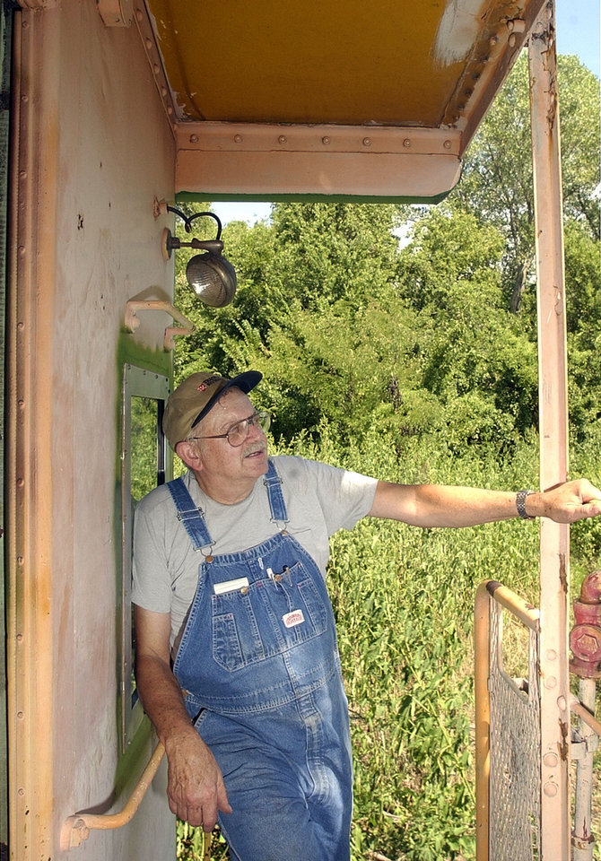 Photo - Jim Murray stands on a caboose during a train ride at the Oklahoma Railway Museum, 3400 NE Grand Boulevard. Visitors to the museum will be able to take a ride on the restored caboose. Staff photo by Nate Billings.