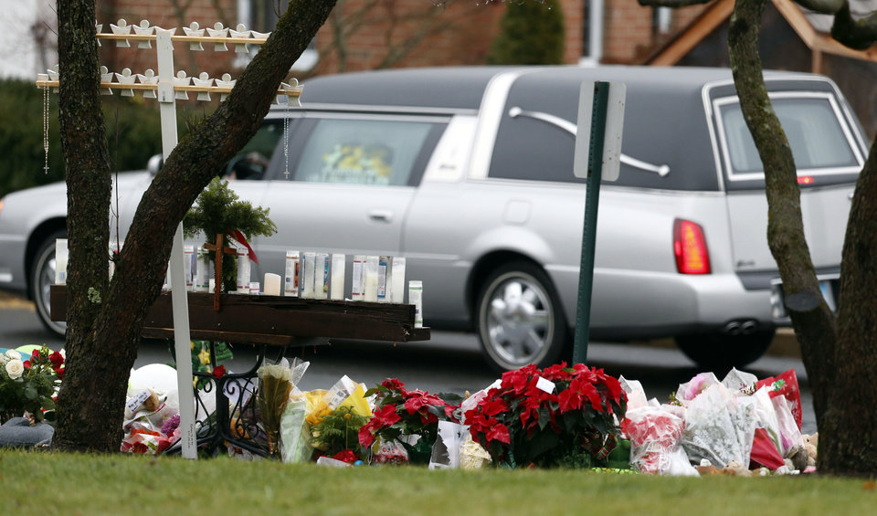 A makeshift memorial stands outside of St. Rose of Lima Roman Catholic Church as the hearse carrying the body of James Mattioli, Tuesday, Dec. 18, 2012, in Newtown, Conn. Mattioli, 6, was killed when Adam Lanza walked into Sandy Hook Elementary School in Newtown, Conn., Dec. 14,  and opened fire, killing 26 people, including 20 children, before killing himself.(AP Photo/Julio Cortez)