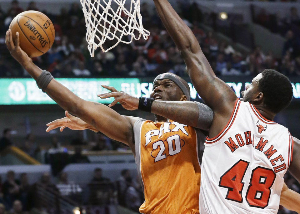 Photo - Phoenix Suns center Jermaine O'Neal, left, drives to the basket against Chicago Bulls center Nazr Mohammed during the first half of an NBA basketball game in Chicago on Saturday, Jan. 12, 2013. (AP Photo/Nam Y. Huh)