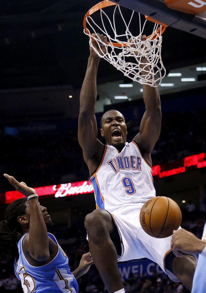 Photo - Oklahoma City's Serge Ibaka (9) dunks over Denver's Kenneth Faried (35) during the NBA preseason basketball game between the Oklahoma City Thunder and the Denver Nuggets at the Chesapeake Energy Arena, Sunday, Oct. 21, 2012. Photo by Sarah Phipps, The Oklahoman