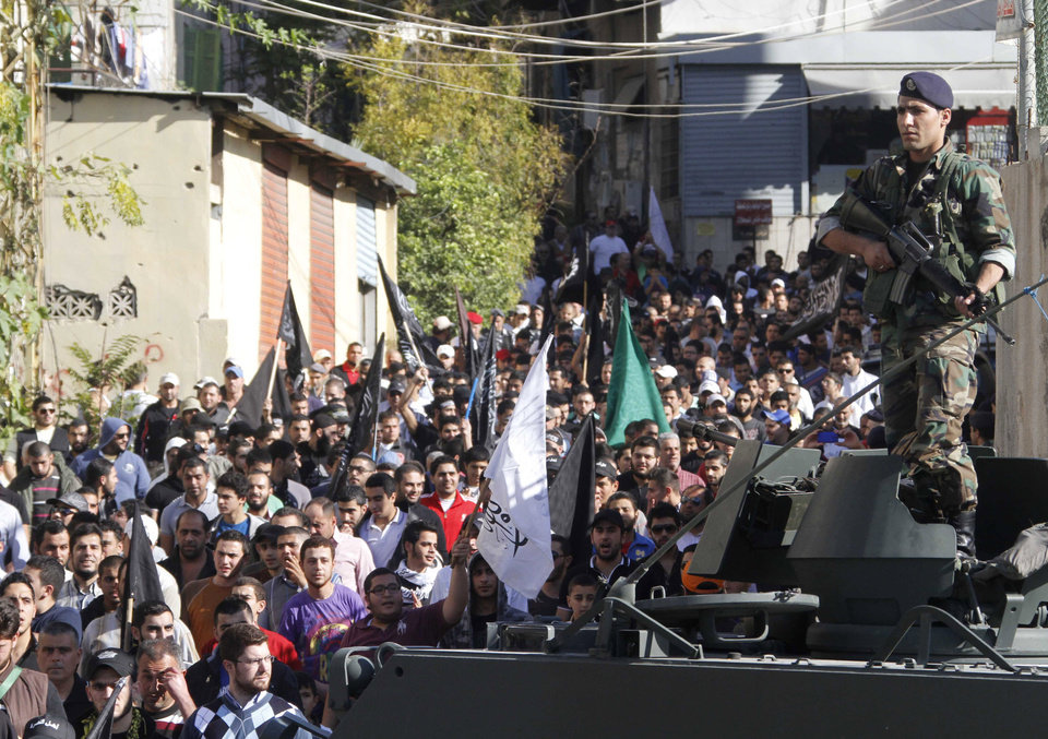 Photo - An army soldier stands guard as supporters of Lebanese anti-Syrian regime and Salafist group leader Sheikh Ahmad al-Assir attend a protest against the Syrian regime in southern port city of Sidon, Lebanon, Sunday, Dec. 2, 2012. (AP Photo/Mohammed Zaatari)