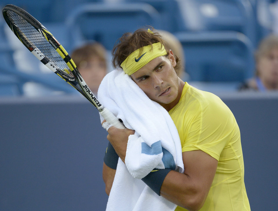 Photo - Rafael Nadal, from Spain, wipes his face during a match against Grigor Dimitrov, from Bulgaria, at the Western & Southern Open tennis tournament, Thursday, Aug. 15, 2013, in Mason, Ohio. (AP Photo/Michael E. Keating)
