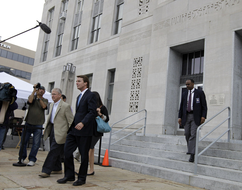Photo -   Former presidential candidate and Sen. John Edwards, center, leaves a federal courthouse in Greensboro, N.C., Tuesday, May 8, 2012. Edwards is accused of conspiring to secretly obtain more than $900,000 from two wealthy supporters to hide his extramarital affair with Rielle Hunter and her pregnancy. He has pleaded not guilty to six charges related to violations of campaign-finance laws. (AP Photo/Chuck Burton)