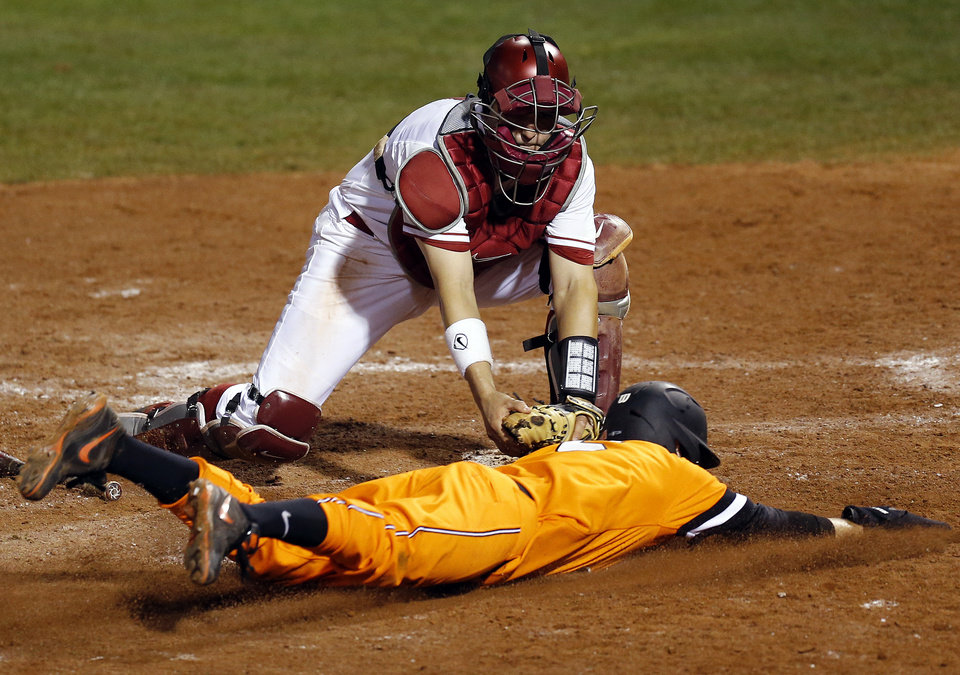 Photo - OU's Anthony Hermelyn (9) tags out OSU's Donnie Walton (5) at home plate in the eighth inning during a Bedlam college baseball game between Oklahoma and Oklahoma State in the Big 12 baseball tournament at the Chickasaw Bricktown Ballpark in Oklahoma City, Friday, May 23, 2014. Photo by Nate Billings, The Oklahoman