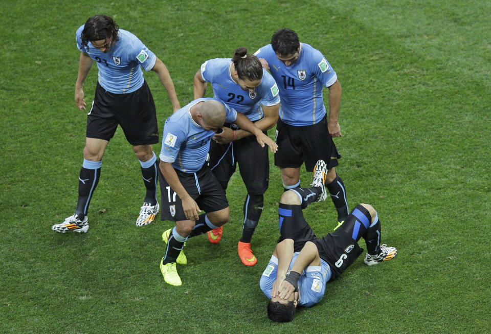 Photo - Uruguay's Luis Suarez, holding his head, is congratulated by teammates after scoring the opening goal during the group D World Cup soccer match between Uruguay and England at the Itaquerao Stadium in Sao Paulo, Brazil, Thursday, June 19, 2014.  (AP Photo/Michael Sohn)