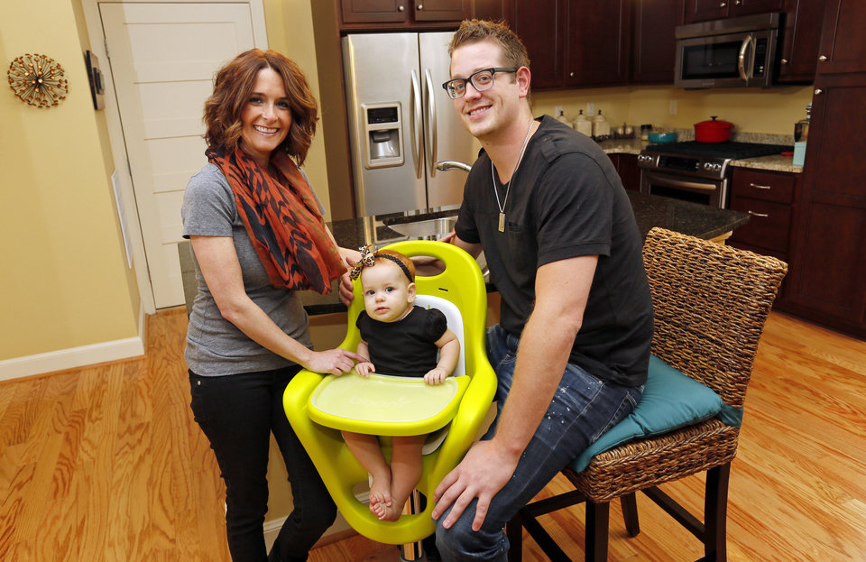 Photo - Kate Jones and Kyle Jones pose for a photo with their 10-month-old daughter, Ramsey Jones, at their Deep Deuce home at The Hill in downtown Oklahoma City, Thursday, Aug. 30, 2012. Photo by Nate Billings, The Oklahoman