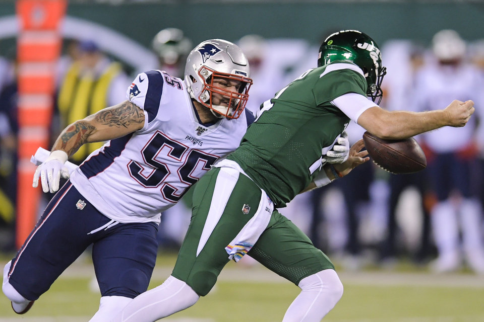 Photo - New York Jets quarterback Sam Darnold, right, loses control of the ball as he is sacked by New England Patriots' John Simon (55) during the first half of an NFL football game Monday, Oct. 21, 2019, in East Rutherford, N.J. (AP Photo/Bill Kostroun)