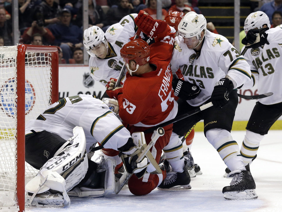 Photo - Detroit Red Wings left wing Johan Franzen (93), of Sweden, is tied up between Dallas Stars defenseman Stephane Robidas (3), wing Michael Ryder (73) and goalie Kari Lehtonen (32) during the second period of an NHL hockey game in Detroit, Tuesday, Jan. 29, 2013. (AP Photo/Paul Sancya)