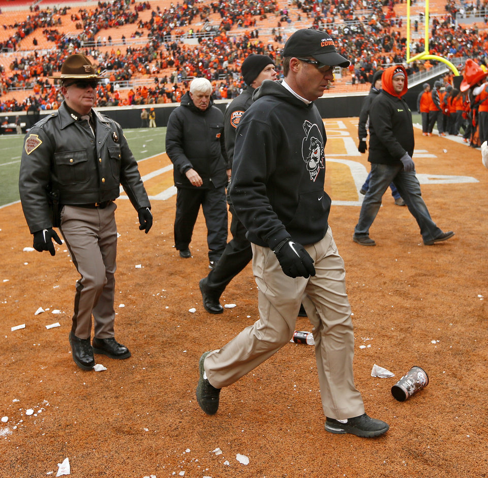 Photo - OSU head coach Mike Gundy leaves the field after the Bedlam college football game between the Oklahoma State University Cowboys (OSU) and the University of Oklahoma Sooners (OU) at Boone Pickens Stadium in Stillwater, Okla., Saturday, Dec. 7, 2013. OU won, 33-24. Photo by Nate Billings, The Oklahoman