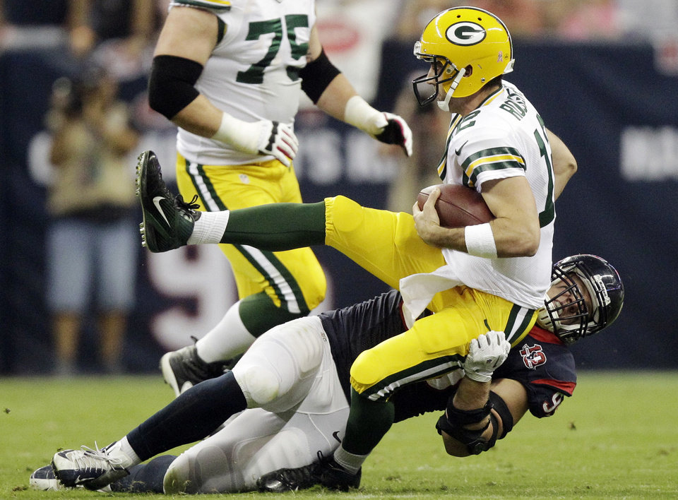 Houston Texans defensive end J.J. Watt, bottom, sacks Green Bay Packers quarterback Aaron Rodgers (12) in the first quarter of an NFL football game, Sunday, Oct. 14, 2012, in Houston. (AP Photo/Patric Schneider)