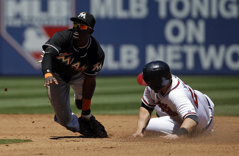 Photo - Miami Marlins' Adeiny Hechavarria, left, falls to the ground after missing the throw at second base as Atlanta Braves' Chris Johnson steals on a wild pitch in the fourth inning of a baseball game, Wednesday, April 23, 2014, in Atlanta. (AP Photo/David Goldman)