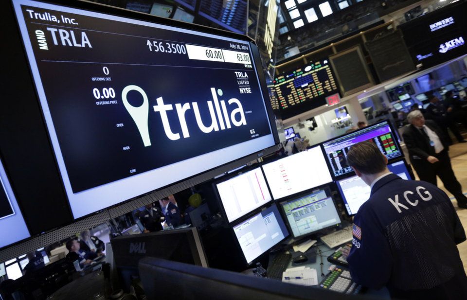 Photo - A specialist woks at the post that handles Trulia on the floor of the New York Stock Exchange, Monday, July 28, 2014. Trulia jumped 11 percent after the real-estate listing service Zillow said it plans to buy it for $3.5 billion. (AP Photo/Richard Drew)