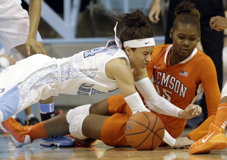 Photo - North Carolina's Jessica Washington, left, and Clemson's Nyilah Jamison-Myers (15) chase a loose ball during the second half of an NCAA college basketball game in Chapel Hill, N.C., Thursday, Jan. 16, 2014. North Carolina won 78-55. (AP Photo/Gerry Broome)