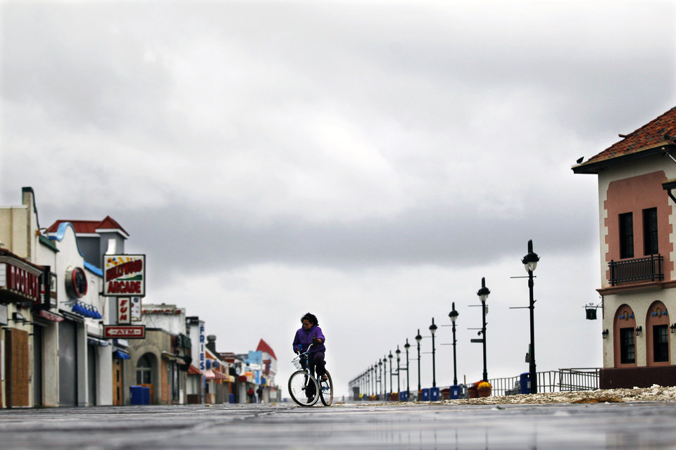 Under threatening clouds, a woman struggles to peddle her bike on the boardwalk Tuesday, Oct. 30, 2012, in Ocean City, N.J., against the high winds coming off the Atlantic Ocean. Sandy, the storm that made landfall Monday, caused multiple fatalities, halted mass transit and cut power to more than 6 million homes and businesses.  (AP Photo/Mel Evans) ORG XMIT: NJME118
