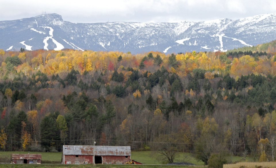 Photo -   FILE-In this Oct. 18, 2010, file photo, sunlight falls on remaining bright foliage as the snow capped ski trails of Stowe ski resort are seen on the side of Mt. Mansfield in Stowe , Vt. Mountain and lake views along with fall foliage can be had for free in Vermont's largest city of Burlington, which feels more like a big town than a city. (AP Photo/Toby Talbot)