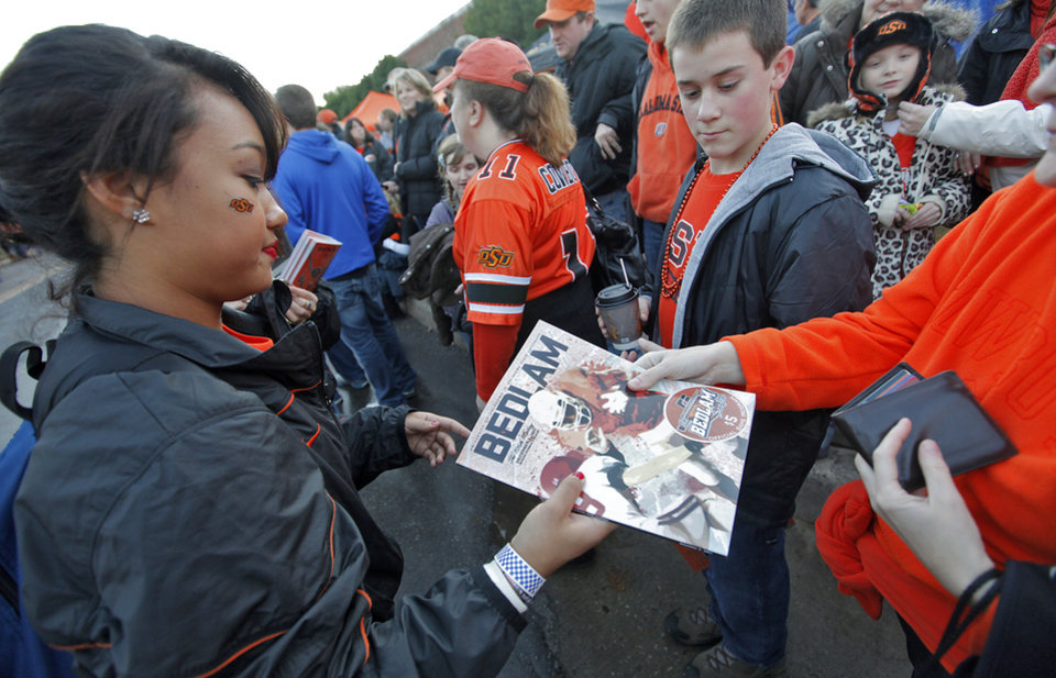 Photo - Oklahoma State student Tiffany Kasai sells Bedlam programs before the Bedlam college football game between the Oklahoma State University Cowboys (OSU) and the University of Oklahoma Sooners (OU) at Boone Pickens Stadium in Stillwater, Okla., Saturday, Dec. 3, 2011. Photo by Chris Landsberger, The Oklahoman
