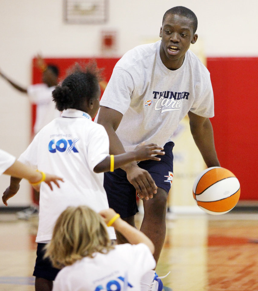 Oklahoma City Thunder draft pick Reggie Jackson works with children during a Thunder Youth Basketball Camp at the Boys and Girls Club of Oklahoma County in Oklahoma City, Saturday, June 25, 2011. The Thunder selected Reggie Jackson with the 24th pick in this year\'s NBA draft. Photo by Nate Billings, The Oklahoman