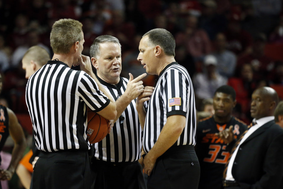 Photo - Game officials discuss a foul during the second half as the University of Oklahoma Sooners (OU) defeat  the Oklahoma State Cowboys (OSU) 77-68  in NCAA, men's college basketball at The Lloyd Noble Center on Saturday, Jan. 12, 2013  in Norman, Okla. Photo by Steve Sisney, The Oklahoman