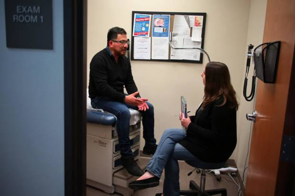 Photo -  Alyssa Cozad, a social work student, talks with client Roberto Hernandez at Good Shepard clinic. [Photo by Doug Hoke, The Oklahoman]