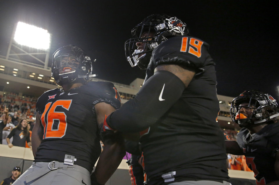 Photo - Oklahoma State's Devin Harper (16), Justin Phillips (19) and Tanner McCalister (2) celebrate a Harper interception for a touchdown in the third quarter during a college football game between Oklahoma State (OSU) and South Alabama at Boone Pickens Stadium in Stillwater, Okla., Saturday, Sept. 8, 2018. Photo by Sarah Phipps, The Oklahoman