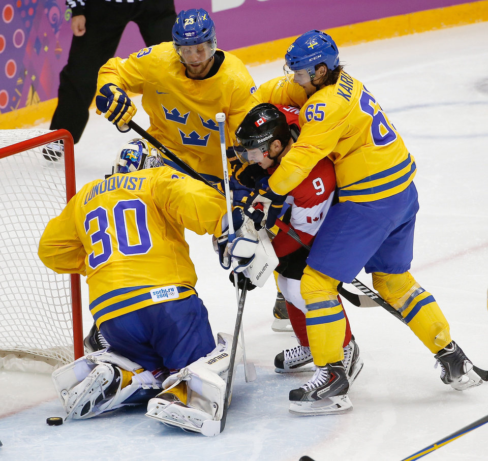 Photo - Alexander Edler (23), Erik Karlsson (65) and goalkeeper Henrik Lundqvist of Sweden (30) surround Matt Duchene of Canada (9) in front of Sweden's goal during the second period of the men's gold medal ice hockey game at the 2014 Winter Olympics, Sunday, Feb. 23, 2014, in Sochi, Russia. (AP Photo/Petr David Josek)